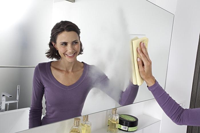 Женщина вытирает зеркало